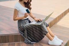 Ung kvinna med bärbara datorn och kreditkorten utomhus Internetshopp Arkivbilder