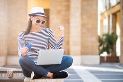 Ung kvinna med bärbara datorn och kreditkorten utomhus Internetshopp Royaltyfri Bild