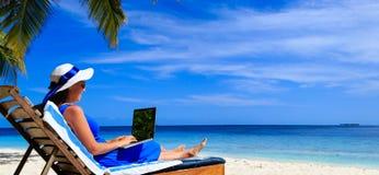 Ung kvinna med bärbara datorn på den tropiska stranden Arkivbilder