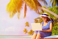 Ung kvinna med bärbara datorn på den tropiska stranden Arkivfoton