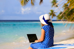 Ung kvinna med bärbara datorn på den tropiska stranden Arkivbild