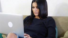 Ung kvinna med bärbara datorn på soffan som arbetar på hennes Start-up affär Arkivbild