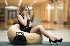 Ung kvinna med bärbara datorn på telefonen arkivbild