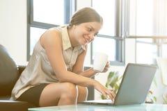 Ung kvinna med bärbara datorn som hemma arbetar i tillfällig atmosfär arkivbilder