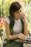 Ung kvinna med bärbara datorn som talar på telefonen Fotografering för Bildbyråer