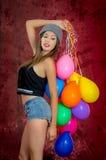 Ung kvinna med ballonger runt om henne, studioskott arkivbild