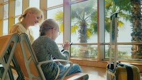 Ung kvinna med barnet i väntande rum för flygplats En flicka av 6 år i exponeringsglas använder en minnestavla Palmträd växer uta lager videofilmer