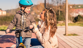 Ung kvinna med barnet över cykeln på solig dag Royaltyfri Foto