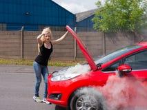 Ung kvinna med bilen på brand Royaltyfri Bild