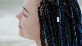 Ung kvinna med blåa flätade trådar för afrikansk kanekalon som går på vinterhavsstranden Afro- frisyr, färgat hår Flicka i vit arkivfilmer