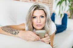 Ung kvinna med blåa kontaktlinser genom att använda den smarta telefonen royaltyfria foton