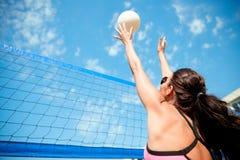 Ung kvinna med bollen som spelar volleyboll på stranden Arkivbild