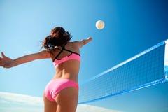 Ung kvinna med bollen som spelar volleyboll på stranden Fotografering för Bildbyråer
