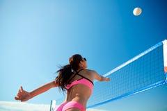 Ung kvinna med bollen som spelar volleyboll på stranden Arkivfoto