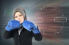 Ung kvinna med boxninghandsken och aggrasive framsidauttryck över abstrakt bakgrund Royaltyfri Bild