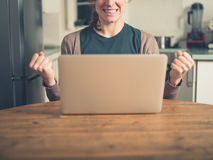 Ung kvinna med bärbar datornäven som pumpar i kök Arkivfoto