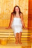 Ung kvinna med brunt hår som tycker om bastuwellness royaltyfri bild