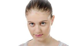 Ung kvinna med bundet hår och att se kameran, på vit backgroun arkivfoto