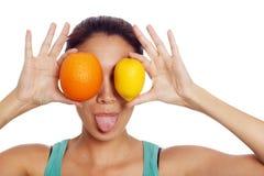 Ung kvinna med citronen och apelsinen Arkivfoton