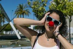 Ung kvinna med clownnäsan Fotografering för Bildbyråer