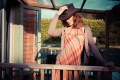 Ung kvinna med cowboyhatten som stading på farstubron av kabinen Arkivbild