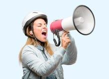 Ung kvinna med cykelhjälmen och hörlurar som isoleras över blå bakgrund royaltyfri foto