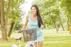 Ung kvinna med cykeln Arkivbild
