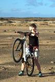 Ung kvinna med cykeln Royaltyfri Fotografi