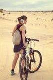 Ung kvinna med cykeln Fotografering för Bildbyråer