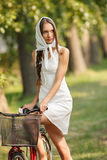 Ung kvinna med cykeln Arkivfoto