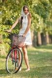 Ung kvinna med cykeln Arkivfoton