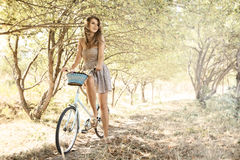 Ung kvinna med cykeln i en park Royaltyfria Bilder