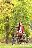 Ung kvinna med cykeln i en parkeraläsebok royaltyfri fotografi