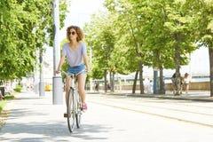 Ung kvinna med cykeln i staden royaltyfria bilder