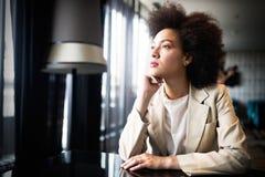 Ung kvinna med den afro frisyren som ler i stads- bakgrund royaltyfria foton