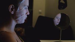 Ung kvinna med den ansikts- arkmaskeringen stock video