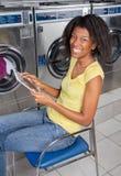 Ung kvinna med den Digital minnestavlan i tvätteri Arkivfoton