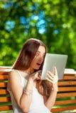 Ung kvinna med den digitala minnestavlan i parkera Arkivfoto