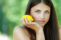 Ung kvinna med den gula citronen Fotografering för Bildbyråer