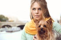 Ung kvinna med den lilla hunden på embarkmenten, väntande vän Fotografering för Bildbyråer