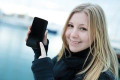 Ung kvinna med den mobil telefonen Arkivfoto