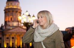 Ung kvinna med den mobila telefonen Arkivbild