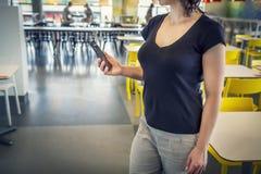 Ung kvinna med den moderna smartphonen i kafét som förbinder till den fria wifien zon Wi-fi i kafé Fritt begrepp för wi fi Royaltyfri Foto