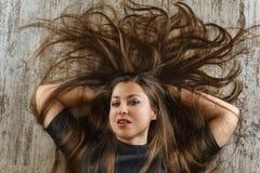 Ung kvinna med den n?tta frisyren som ligger p? golvet Top besk?dar royaltyfri bild
