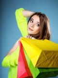 Ung kvinna med den pappers- mång- färgade shoppingpåsen Royaltyfria Bilder