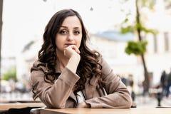 Ung kvinna med den unga härliga vita kvinnan för långt brunt hår med lockigt brunt hår på en tabell mot bakgrunden av gatan arkivbilder