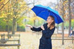 Ung kvinna med det blåa paraplyet i den Luxembourg trädgården av Paris på en regnig dag för nedgång eller för vår Royaltyfria Bilder