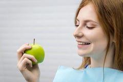 Ung kvinna med det stickande gröna äpplet för sund tand royaltyfri fotografi