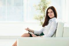 Ung kvinna med digitalt minnestavlasammanträde i lobbyen av kontoret royaltyfria foton