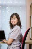 Ung kvinna med en bärbar dator royaltyfri bild